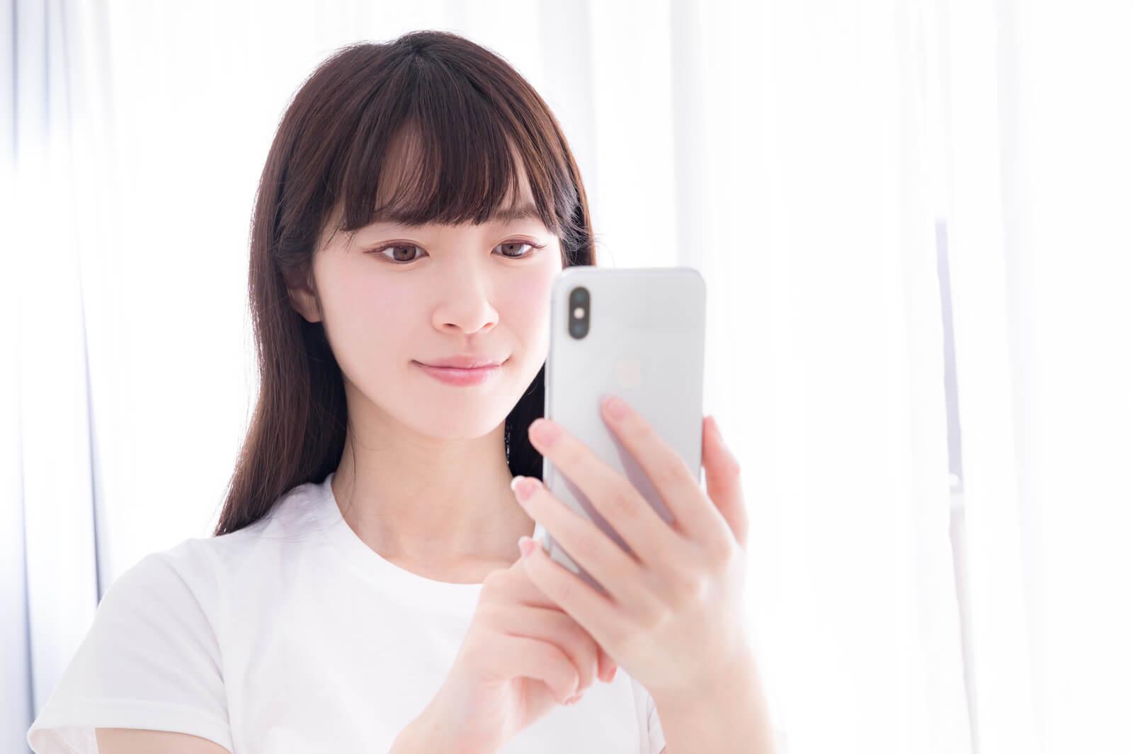 スマホで個人輸入代行サイトを閲覧する女性のイメージ画像