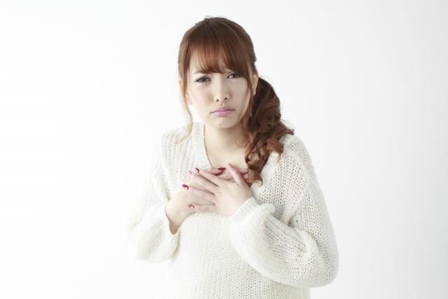 胸をおさえる女性のイメージ画像